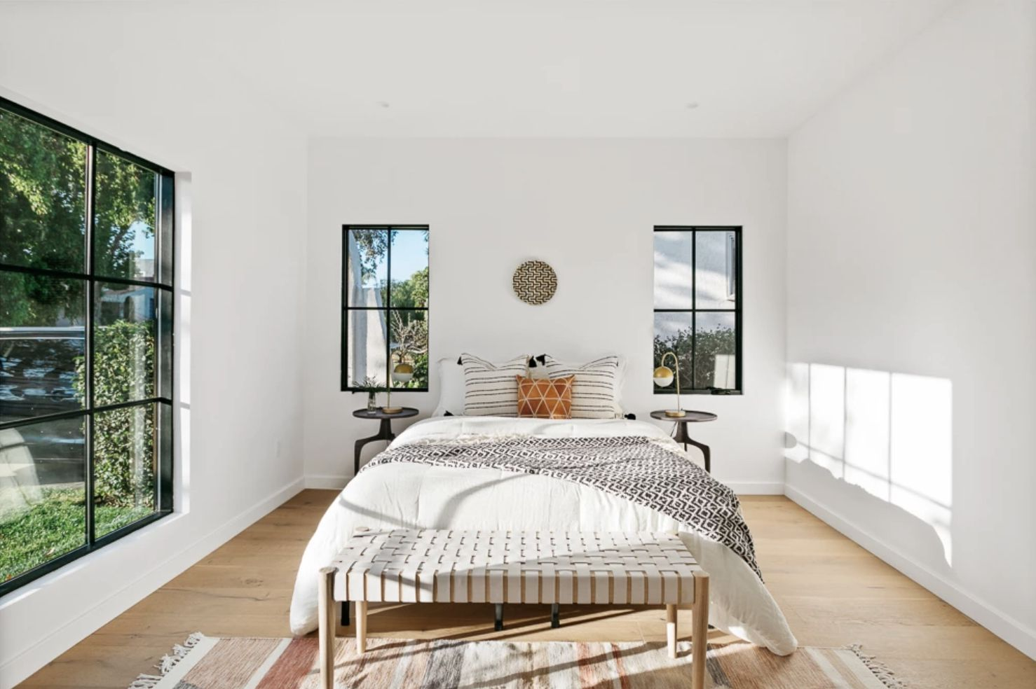 minimalist bedroom with open windows, white walls, small pop or orange color on the bed