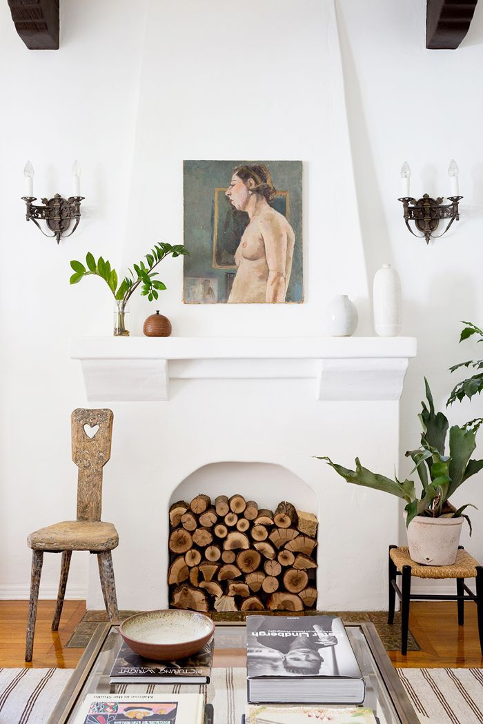a streamlined living room with a white fireplace filled with logs