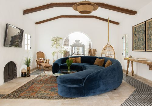 living room with blue velvet couch and vintage furnishings