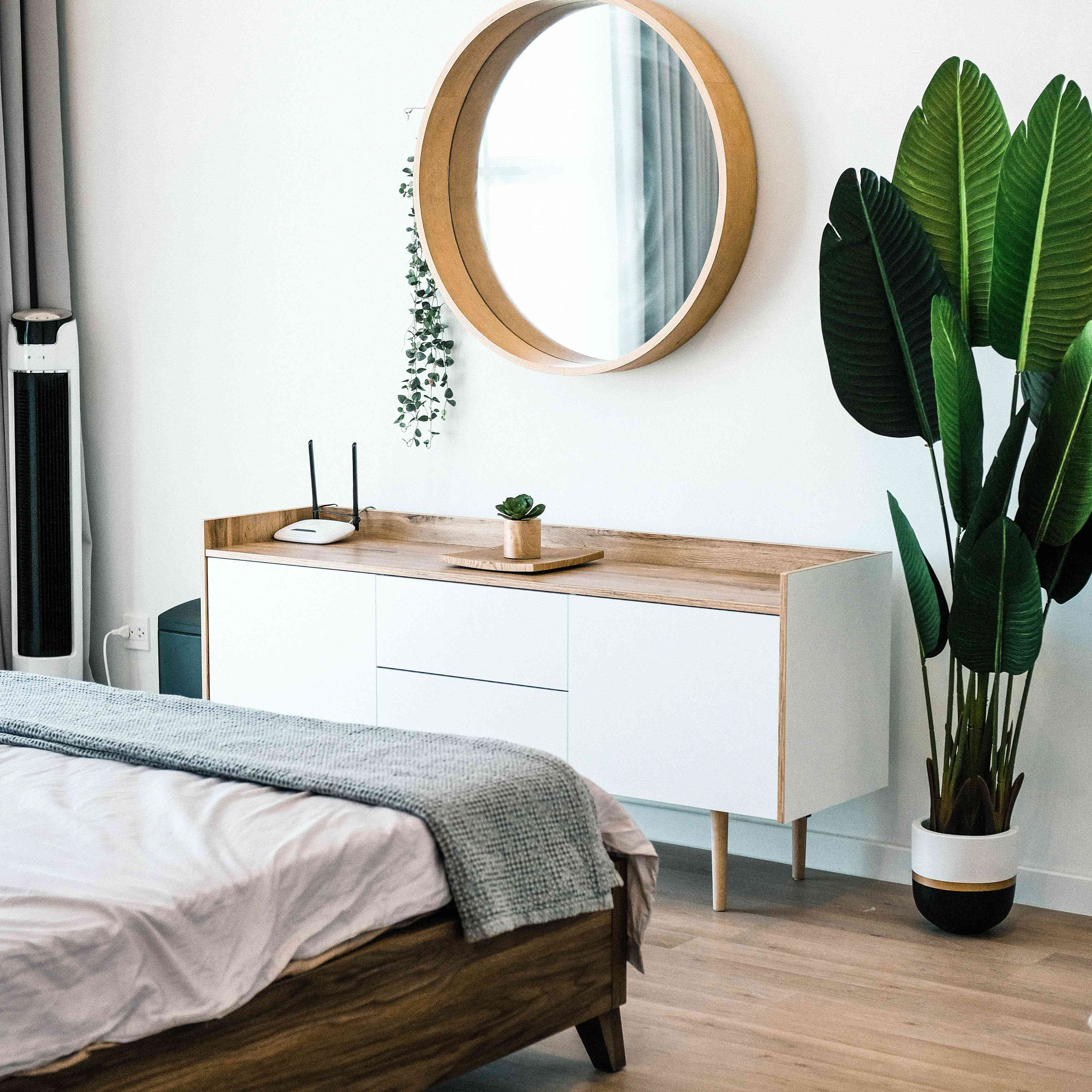 bedroom with platform bed, white dresser, and round mirror on the wall
