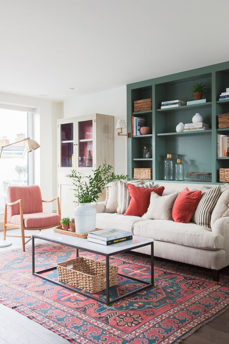 Pink neutral living room with green built-in shelves.