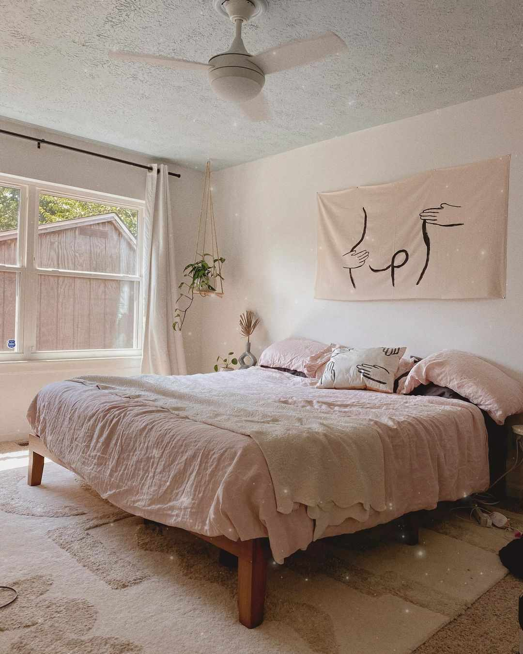Neutral bedroom with pink bed linens and hanging plant.