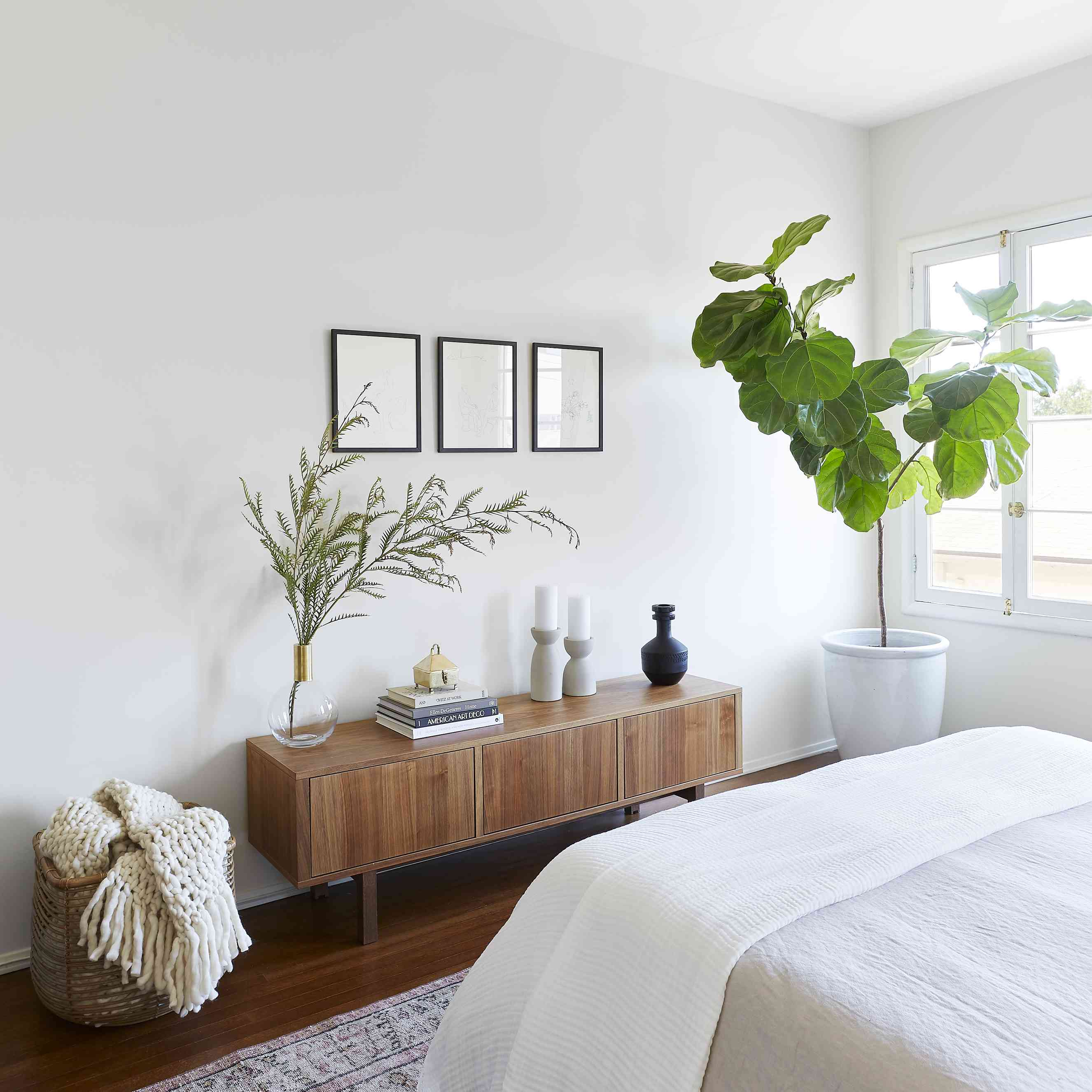 bedroom with wood credenza and fiddle leaf fig tree