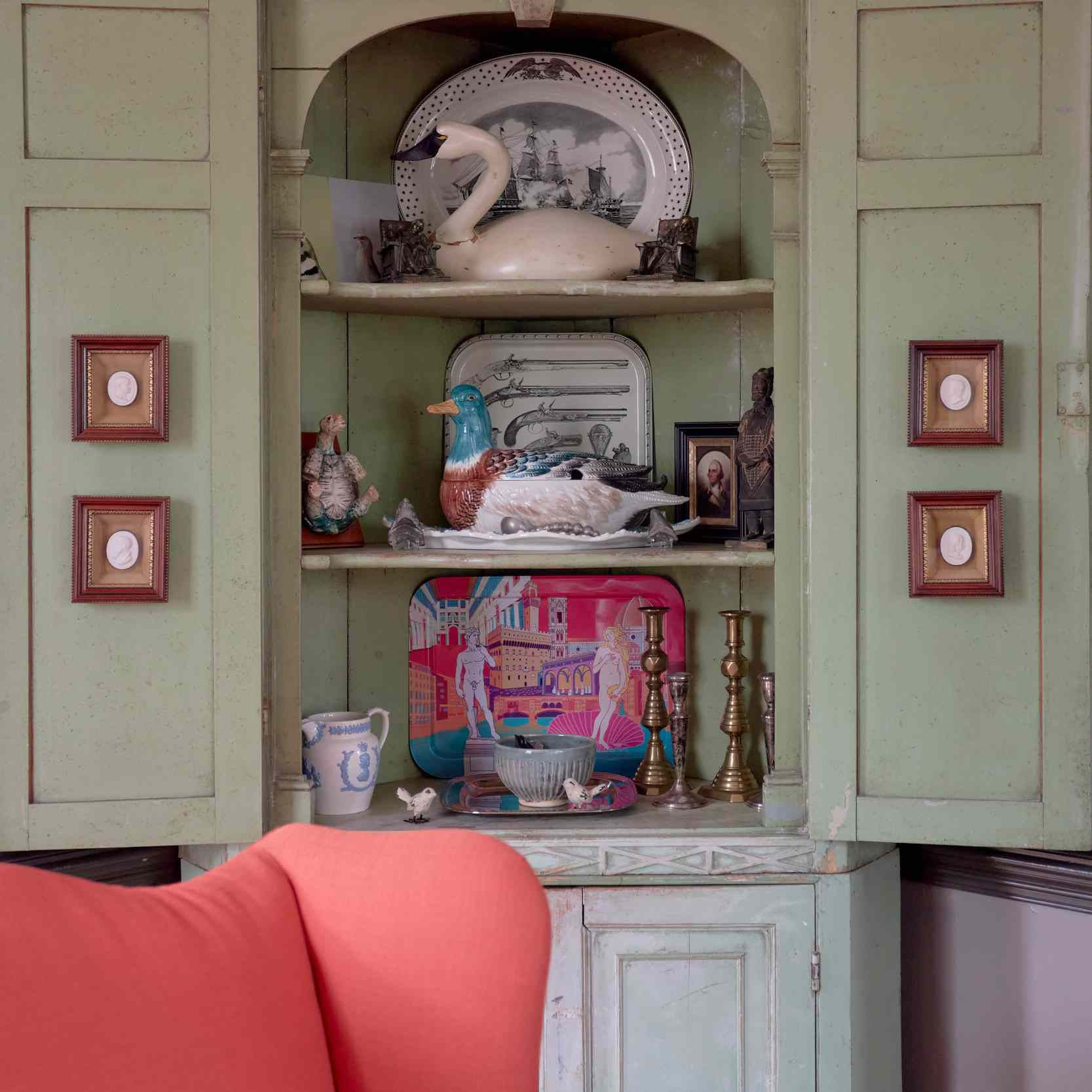 Mint green china cabinet with goose sculpture.