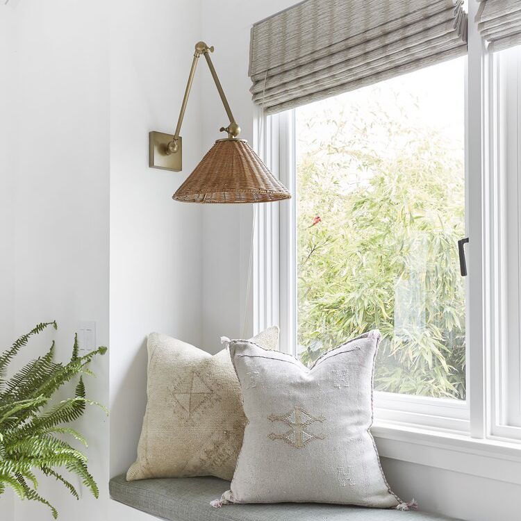 A window seat with cushions and a wall sconce