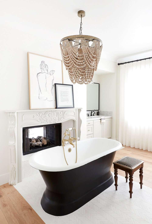 A bathroom with a black bathtub and a beaded chandelier