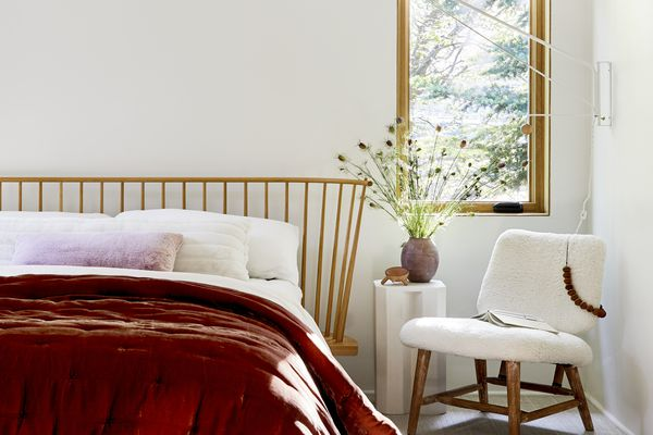 sunny bedroom with dark orange velvet quilt