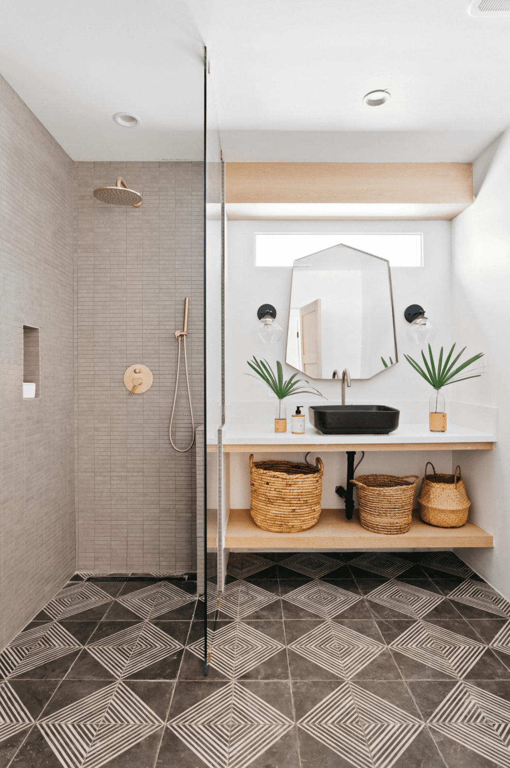 A small primary bathroom, which has been lined with the same striking floor tile from wall to wall