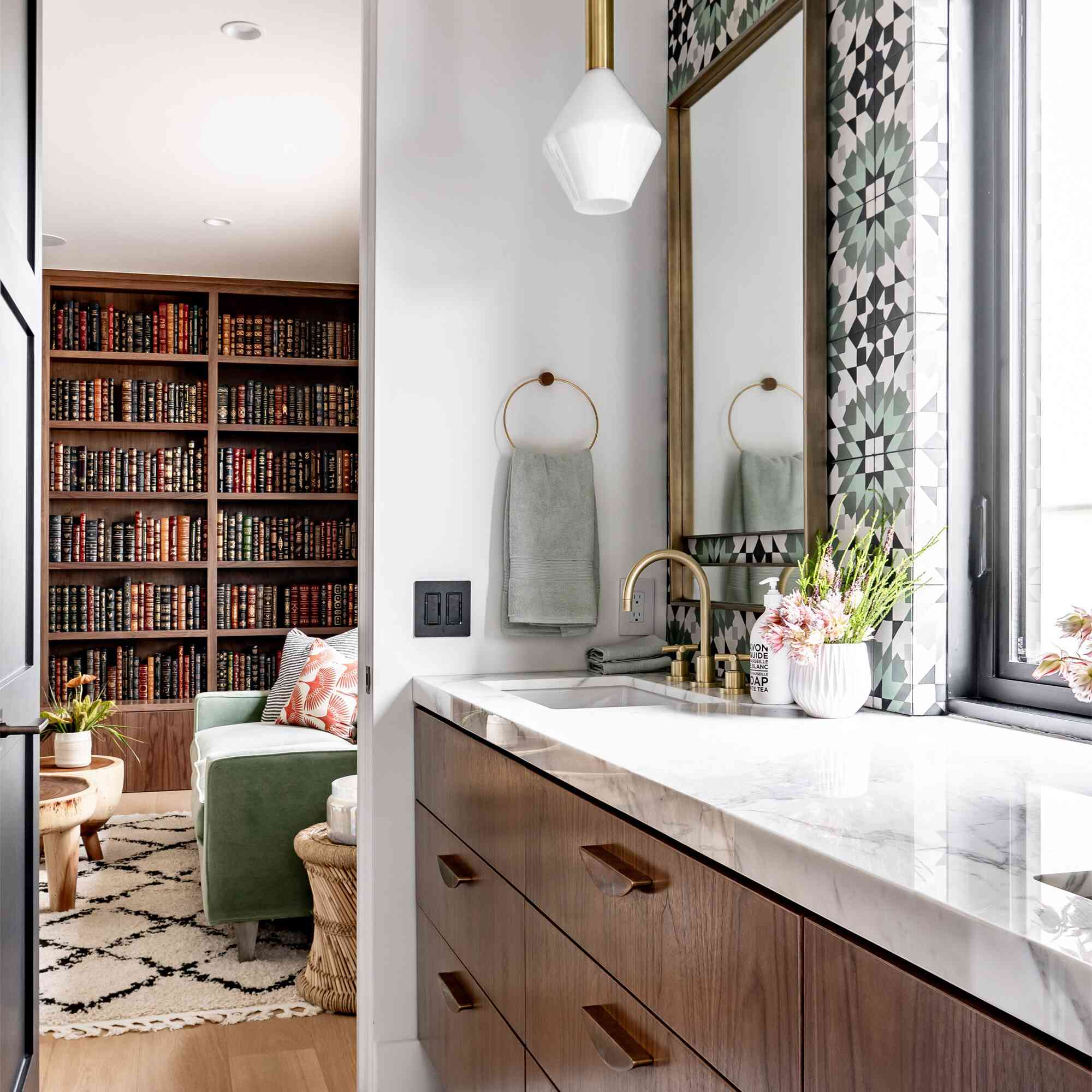 Modern bathroom with graphic tile and a view into a library room
