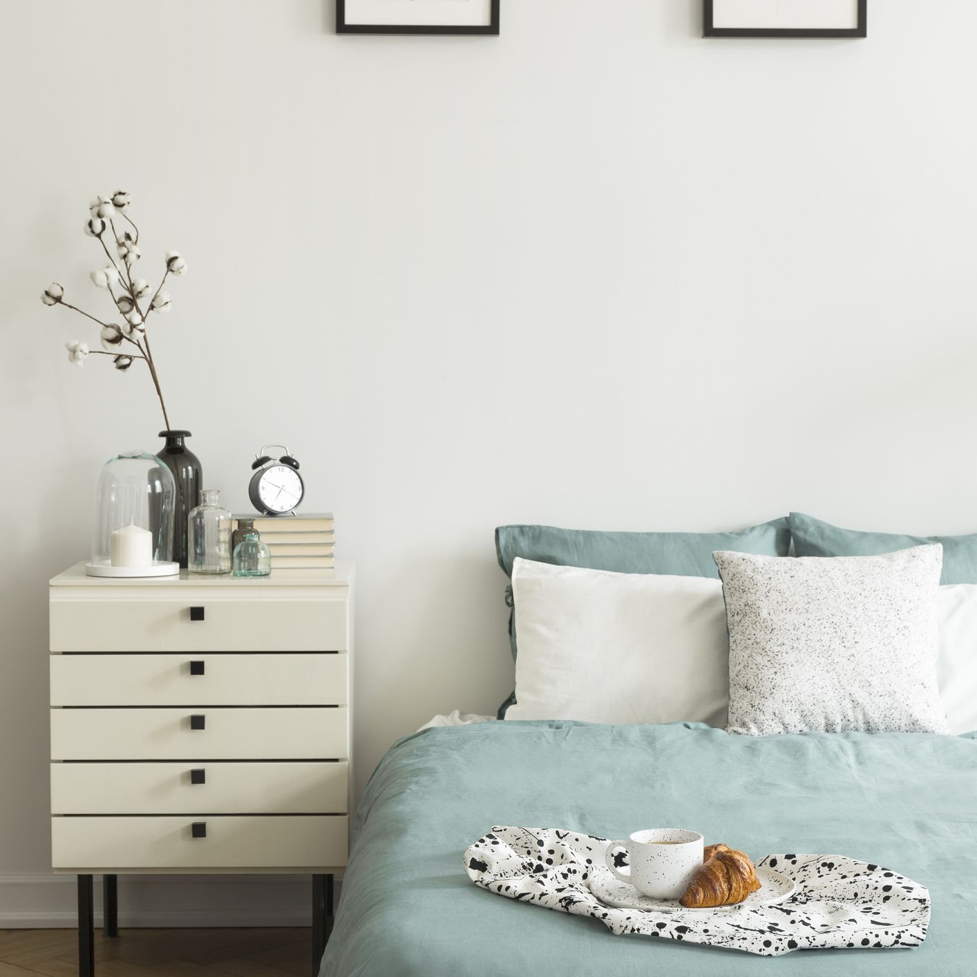 Real photo of white bedroom interior with breakfast placed on bed with pillows and pastel green bedclothes, two simple posters and bedside table with decor