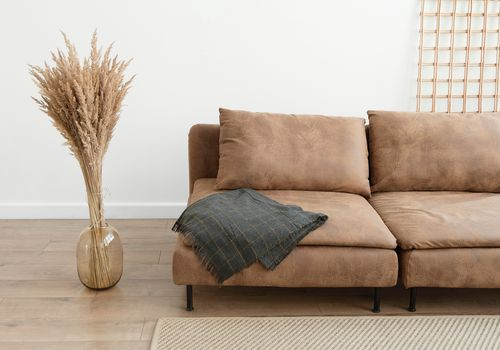 pampas grass next to a leather sofa