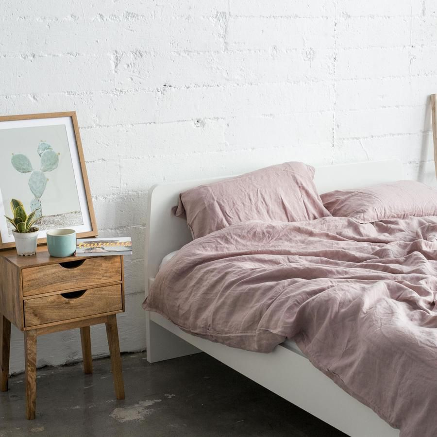A messy bed made with rumpled pink sheets.