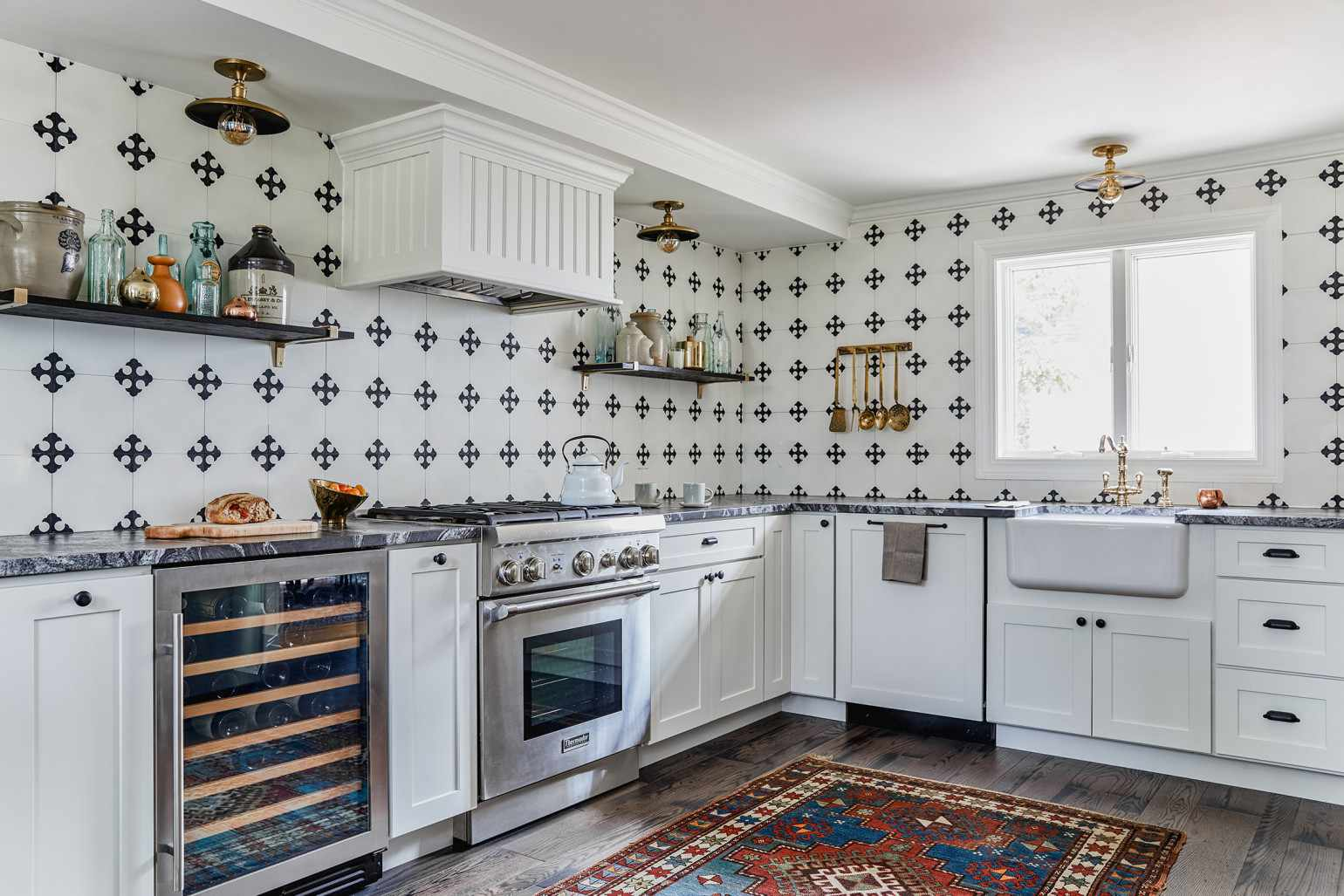 A kitchen with a bold tiled backsplash and a printed red rug on the floor