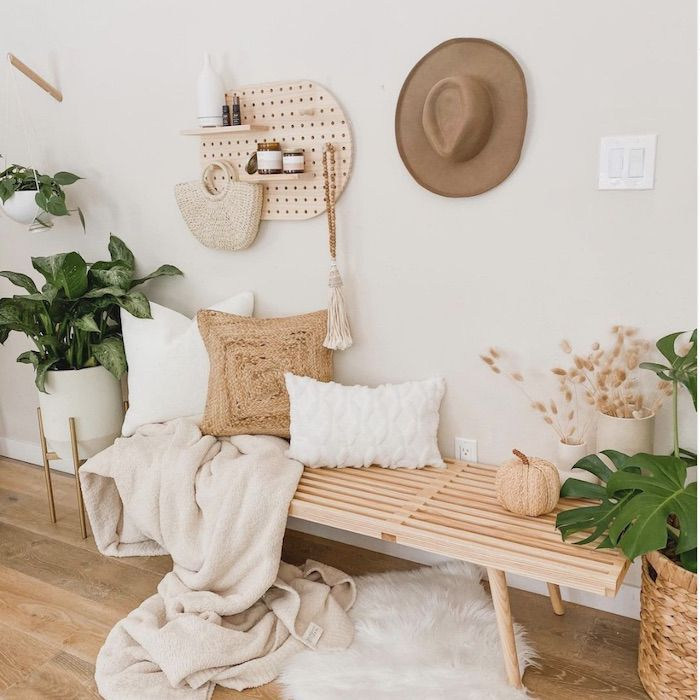 white and wood entryway, wood bench, hat and decorative hanger on wall, white fur rug on ground