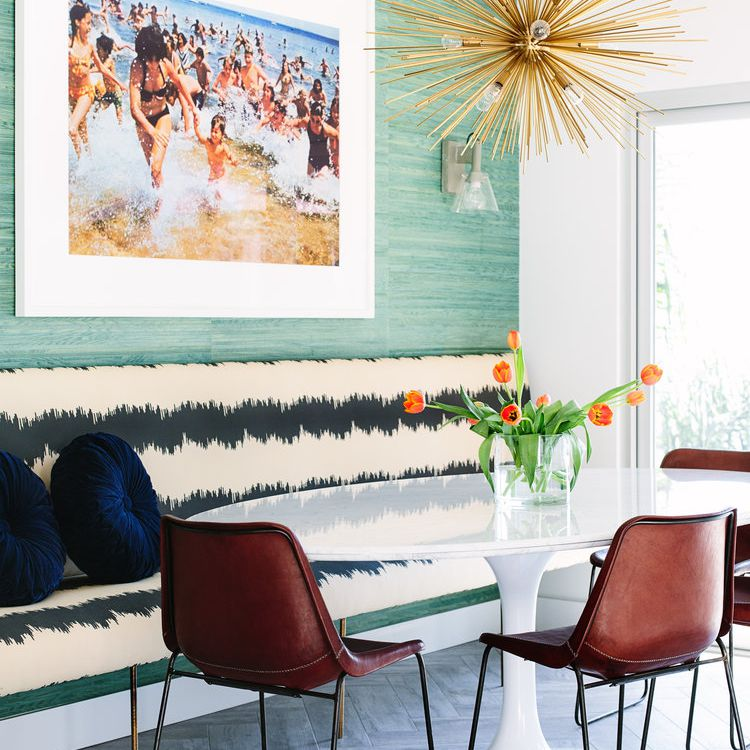 Eclectic breakfast nook features large-scale art, midcentury modern statement light