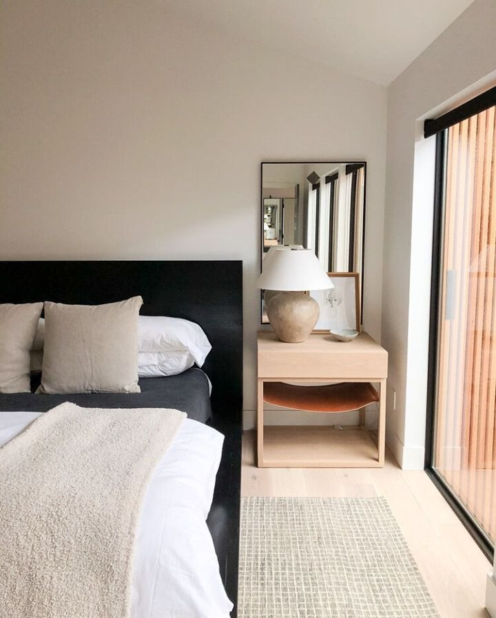 Neutral bedroom with black headboard and light wooden side table.