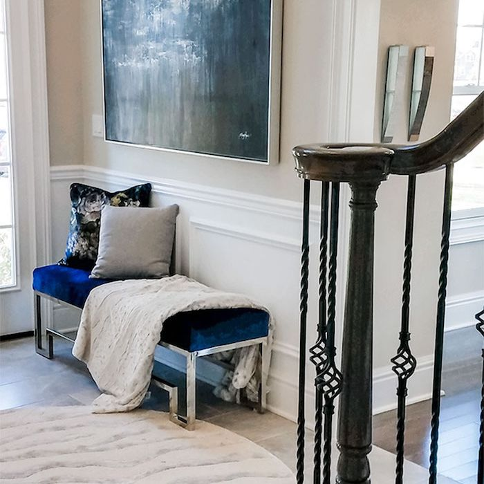 entryway with large painting, blue velvet bench, textured print rug