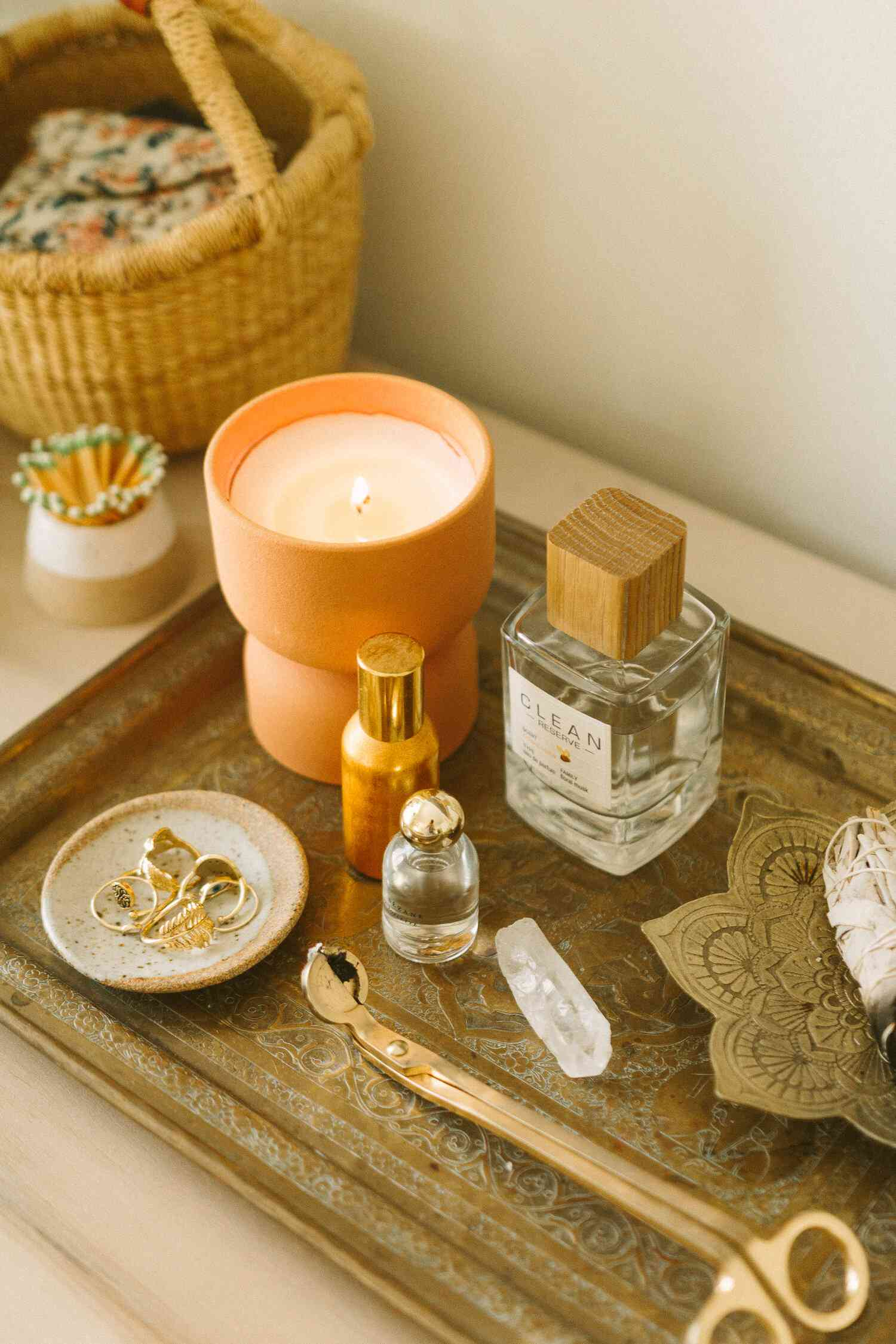 Decorative tray holding a candle, perfume, and jewelry