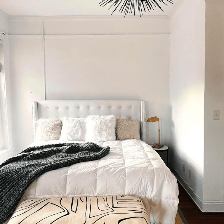 small bedroom with white walls, headboard, and bedding