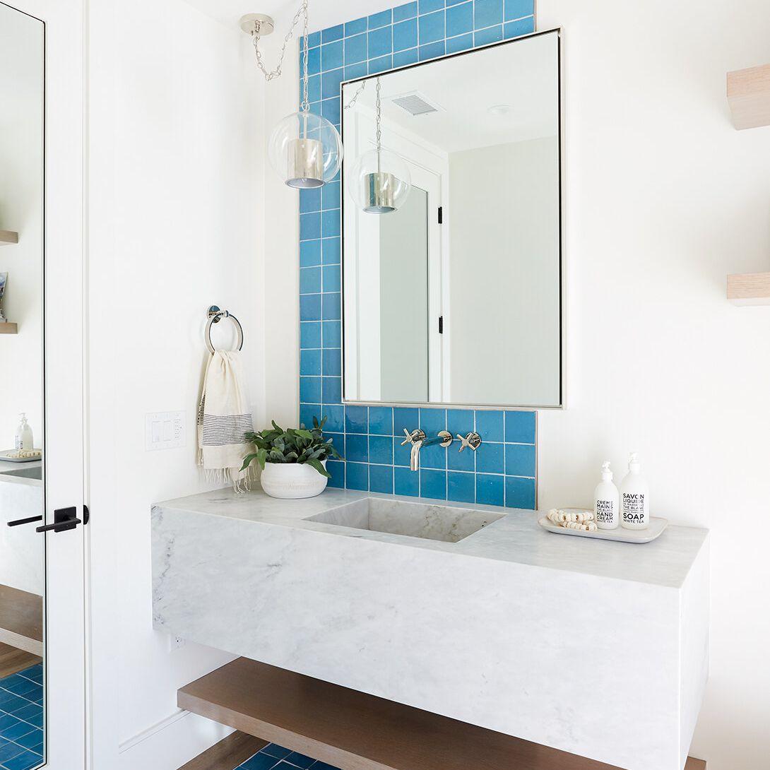 A bathroom with an asymmetrical blue tiled backsplash