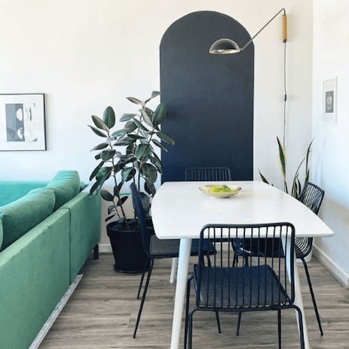 Dining table in front of black painted arch.