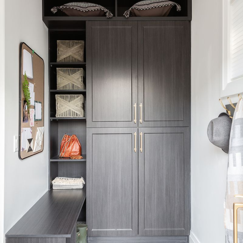 A mudroom with floor-to-ceiling cabinets and shelves
