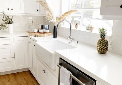 Cocina blanca con lavavajillas.