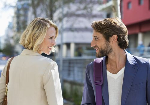 woman and man smiling at each other on the street