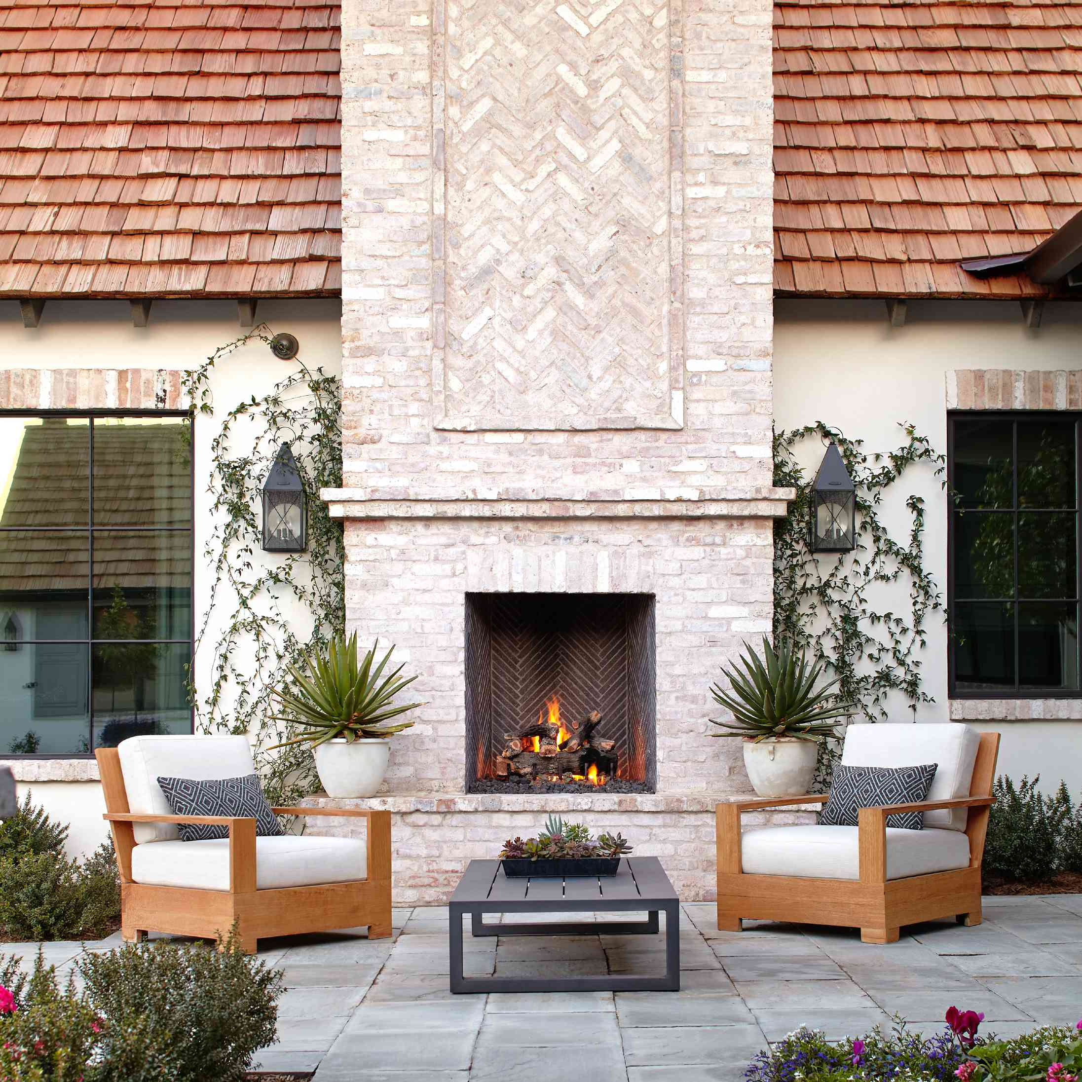 An outdoor fireplace with an extra-tall chimney, built directly against a home