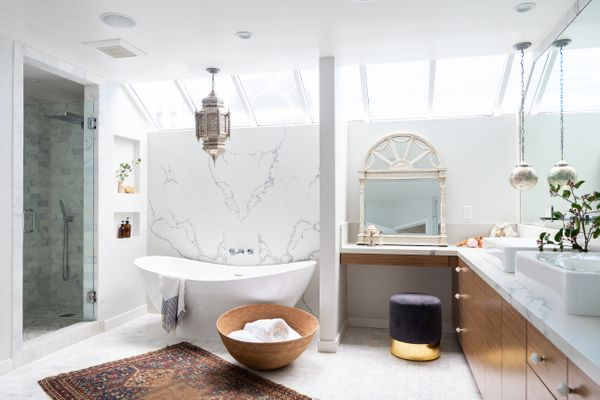 bathroom with large tub, moroccan lamps, and large french mirror