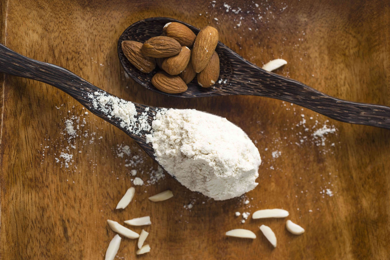 Almendras y harina de almendras en cucharas de madera.