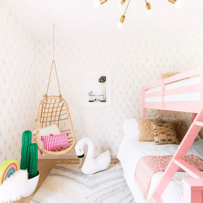 Statement brass chandelier in teen bedroom with hanging rattan chair and pink bunk beds.