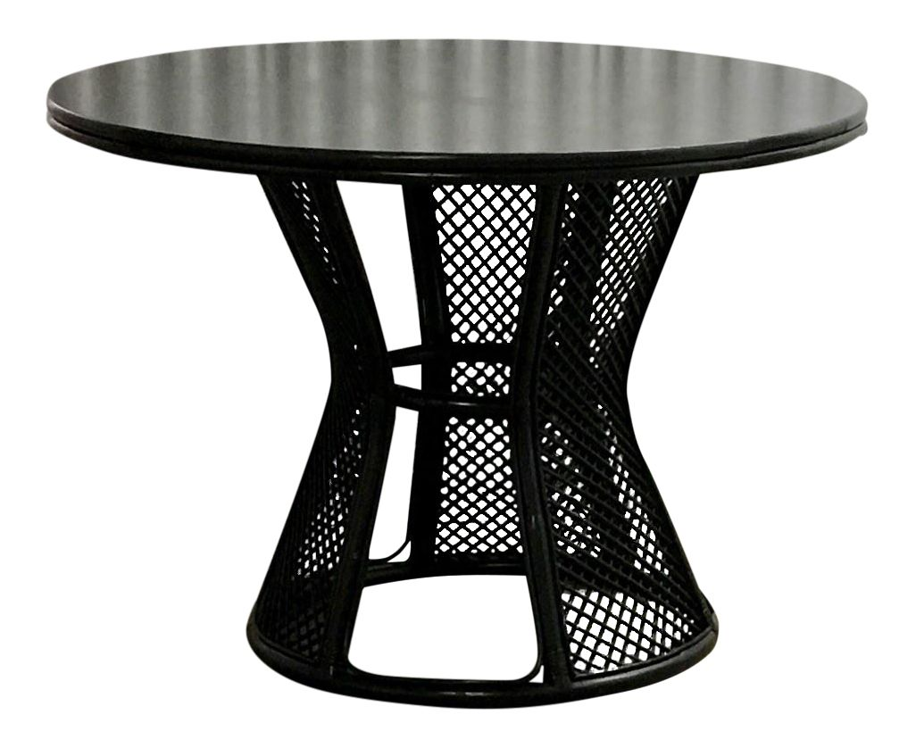 Black round dining table with high-gloss tabletop and rattan base.