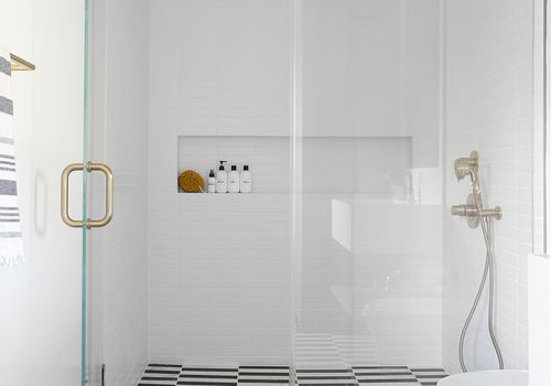 walk-in shower with patterned tile floor