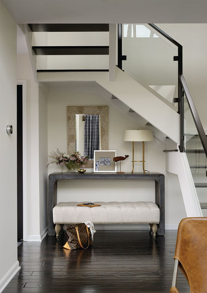 an organized entryway with a console and bench