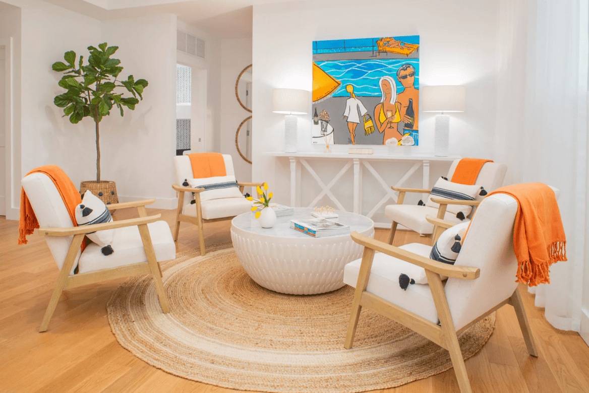 A white living room with blue and orange accents