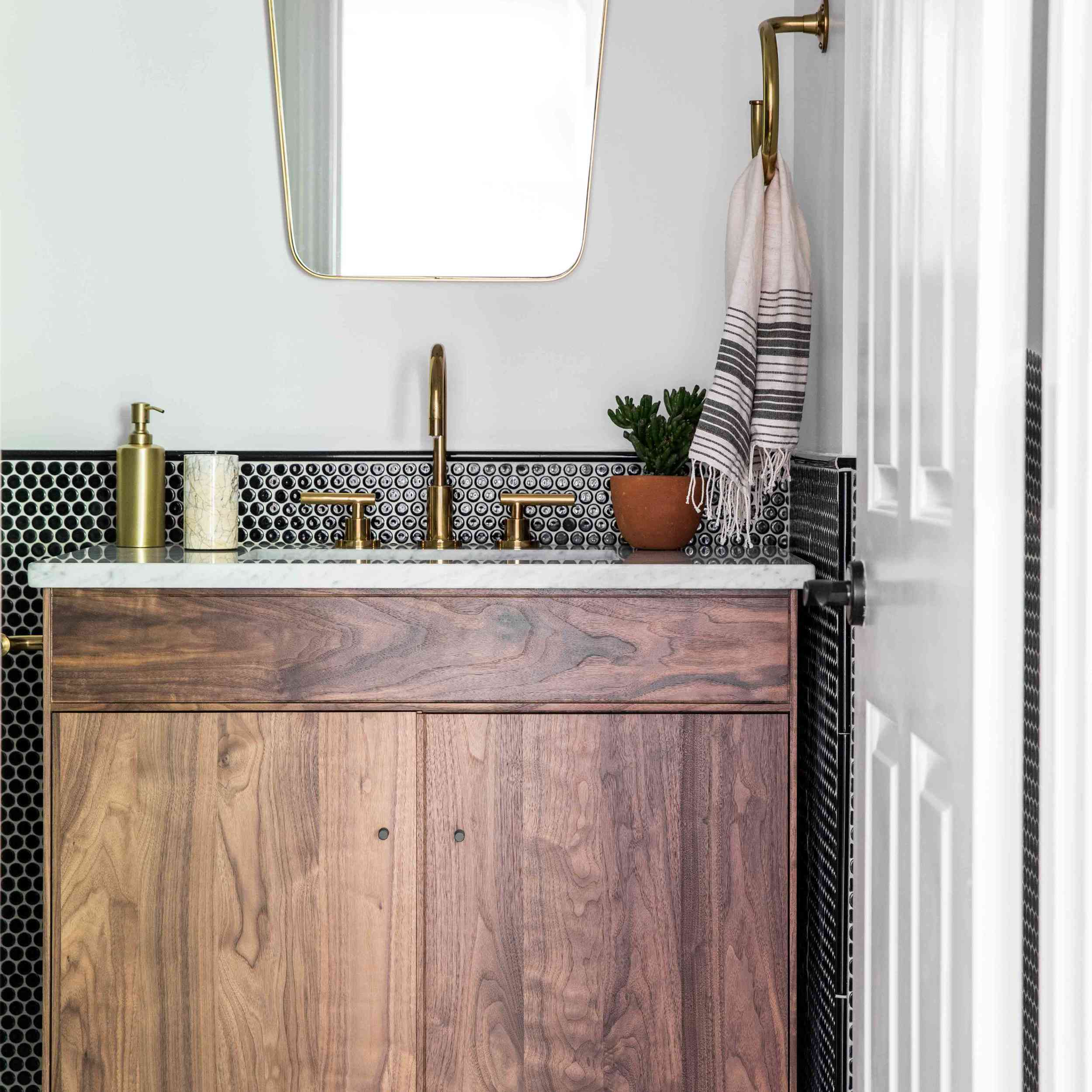 A bathroom with a two-tone wall crafted from white paint and black penny tiles