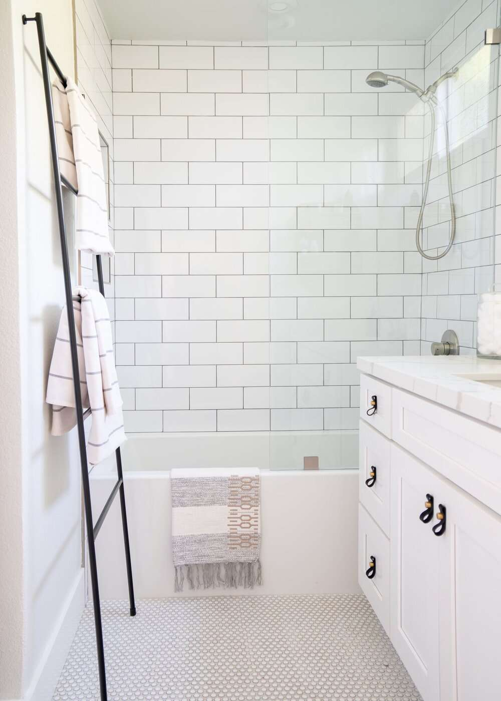 A small all-white primary bathroom decorated with a ladder that's been repurposed as a towel rack