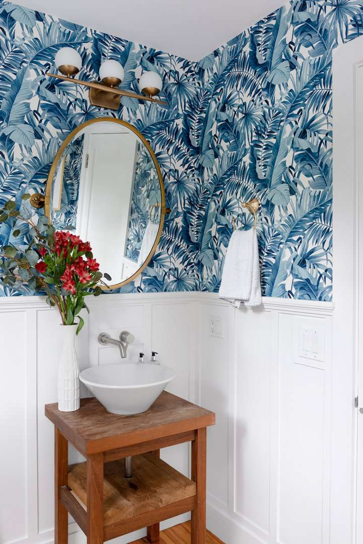 bathroom with blue wallpaper and small pedestal sink