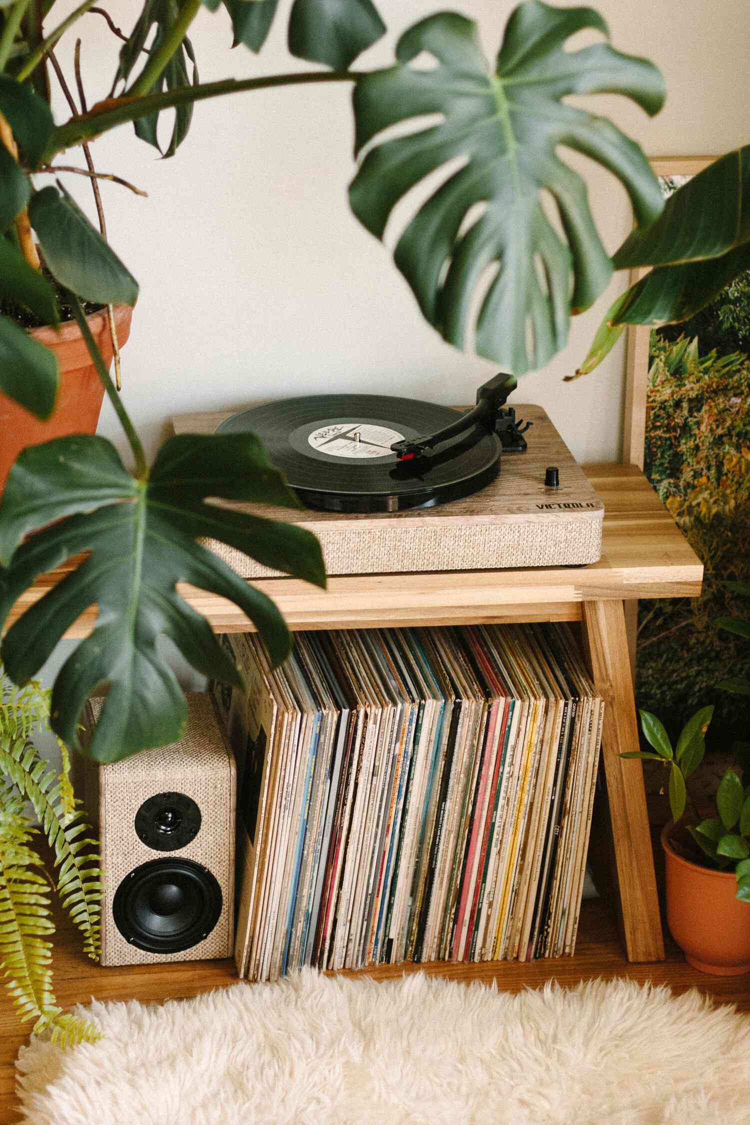 Wooden bench topped with record player, stacked records and a speaker beneath
