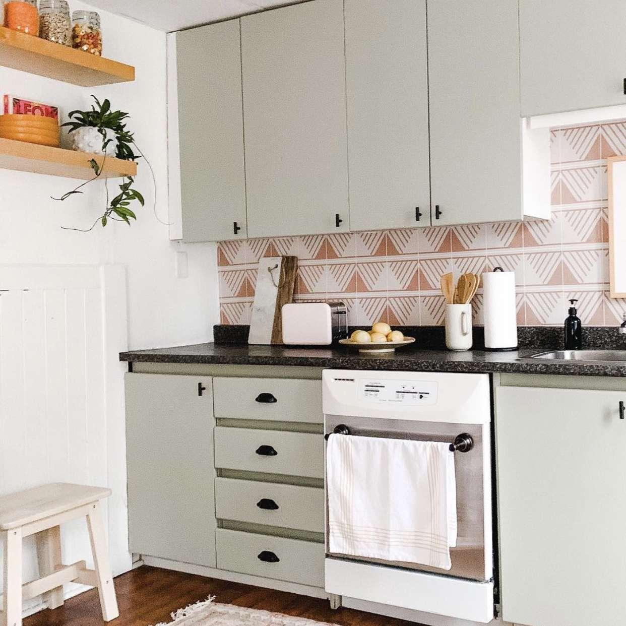 Sage green kitchen cabinets with pink backsplash.