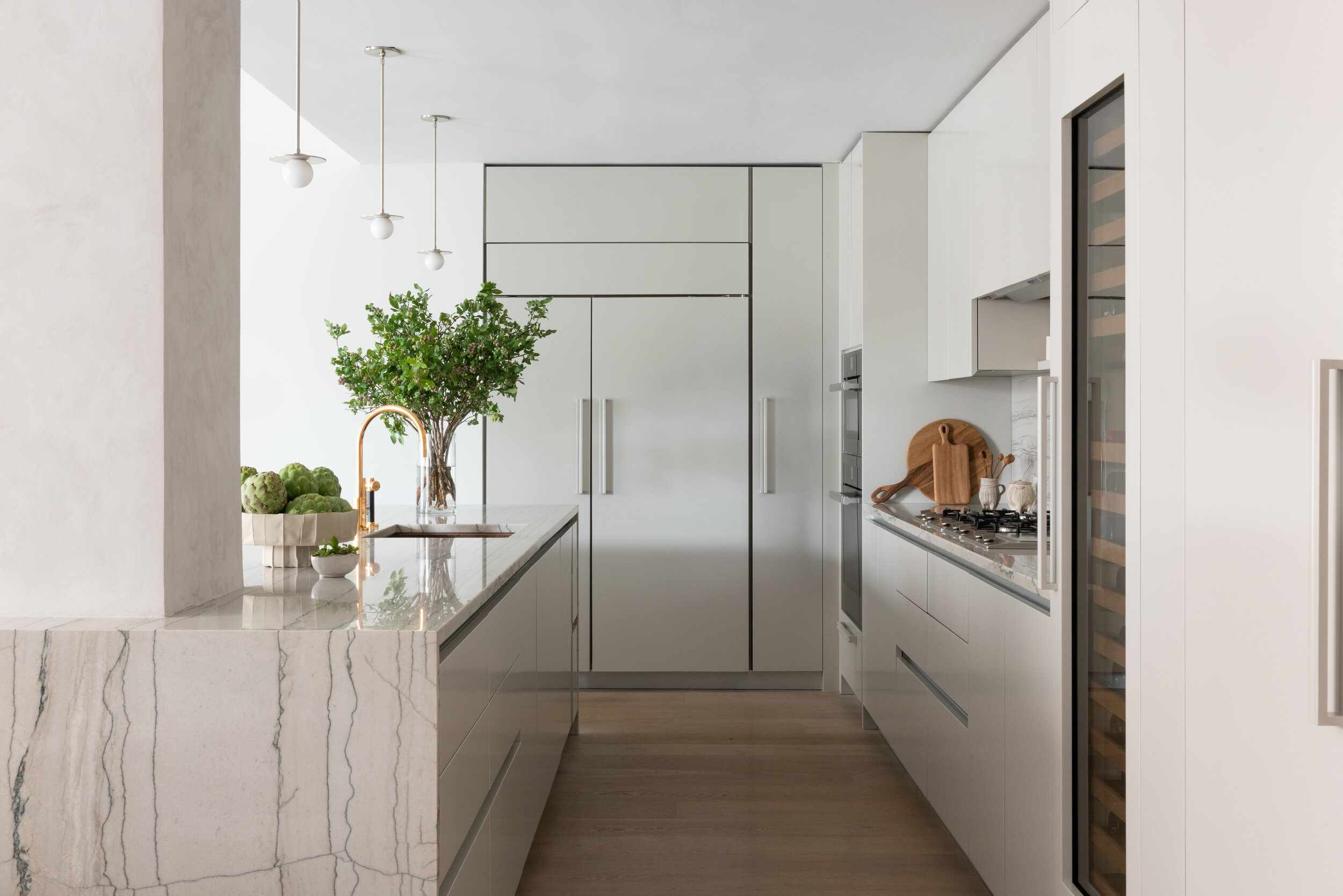 A kitchen with light gray cabinets and marble countertops