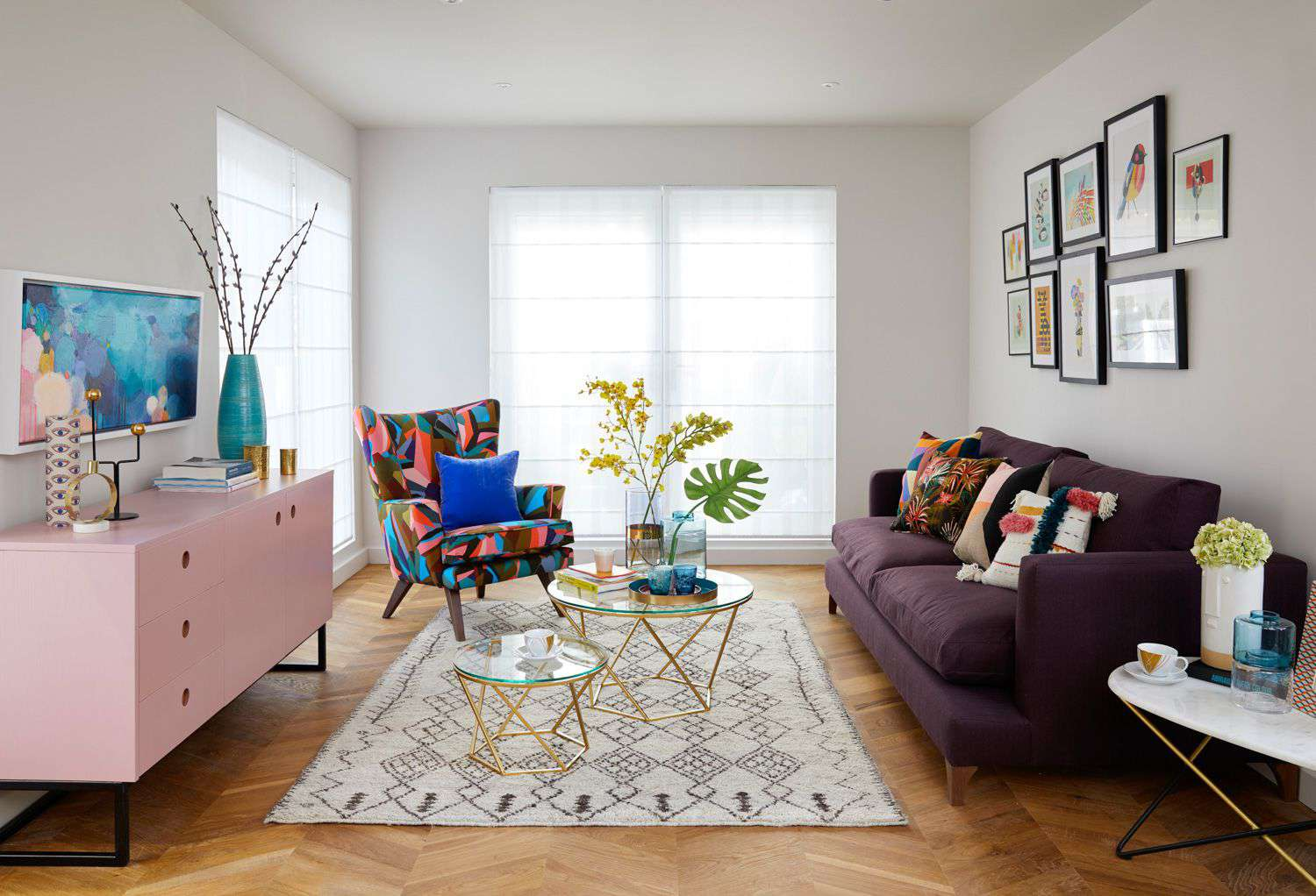 Eclectic living room with purple couch and pink console