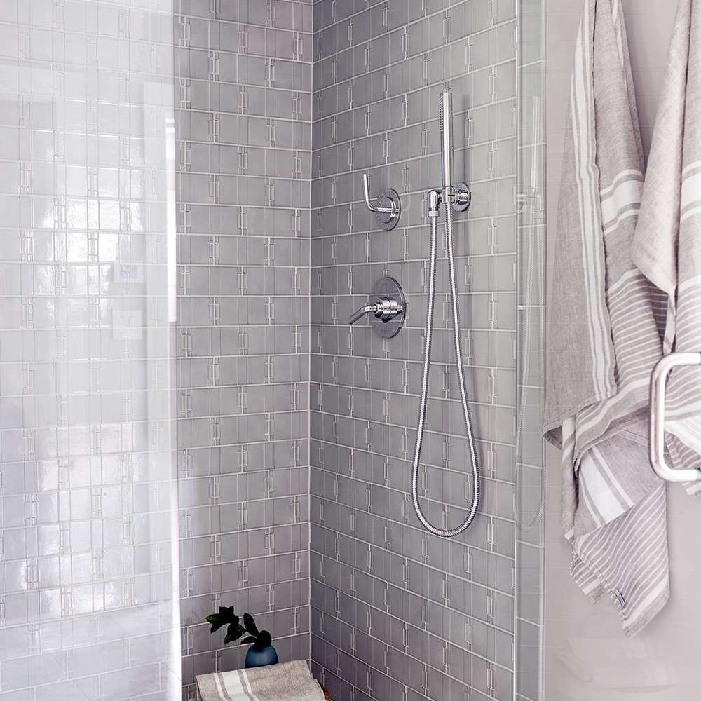 A shower lined with gray tiles