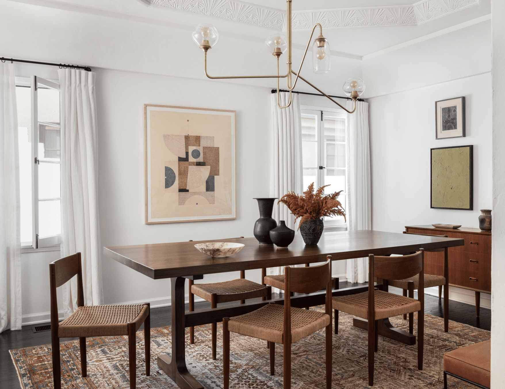 A dining room featuring a work of beige and pink art