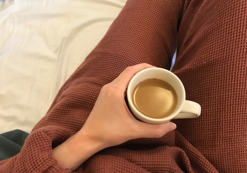 parachute lounge set review - holding cup of coffee in bed with lounge set