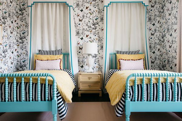 Bedroom with two twin canopy beds, whimsical wallpaper, and yellow bedding.