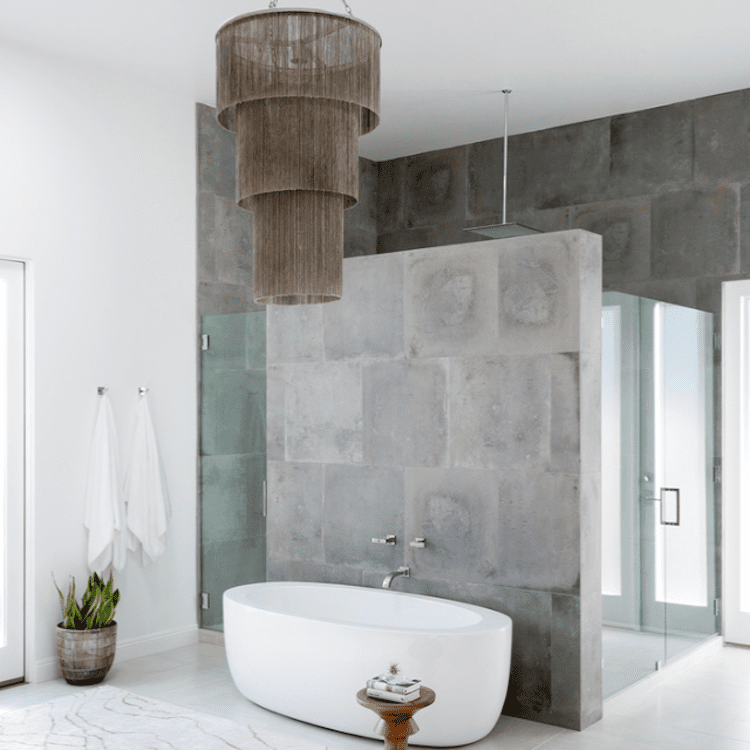 A gray bathroom with cement walls and a large chandelier