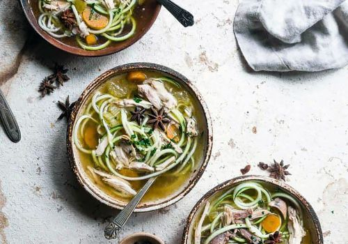 Several bowls of chicken zoodle keto-approved soup.
