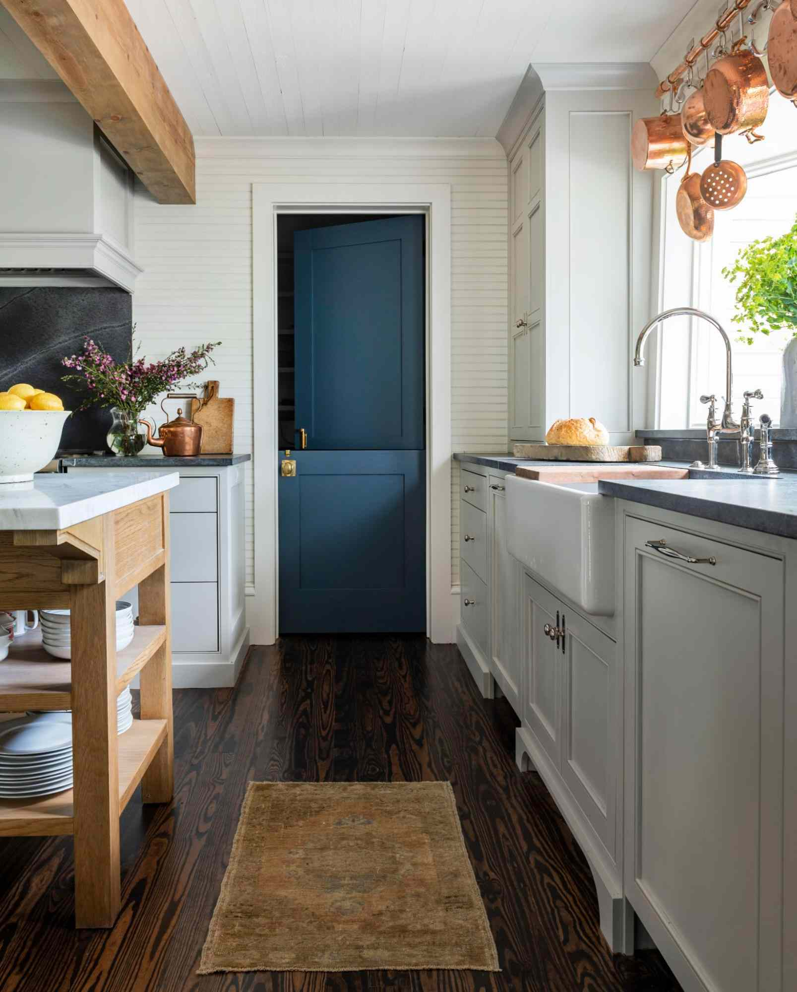 Rich teal door in white kitchen.